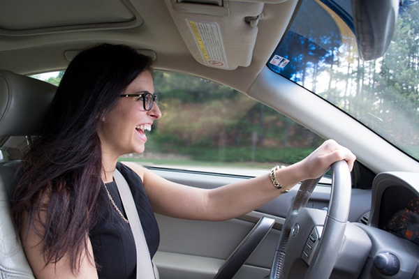 woman laughing while she drives and holds the steering wheel