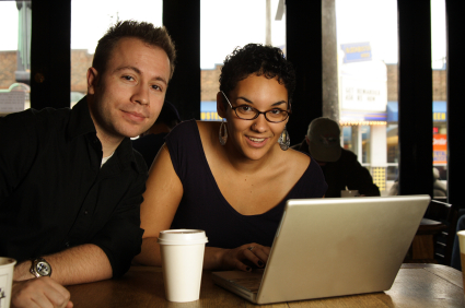 a man and women at a counter next to a computer laptop with a drink cup collaborating