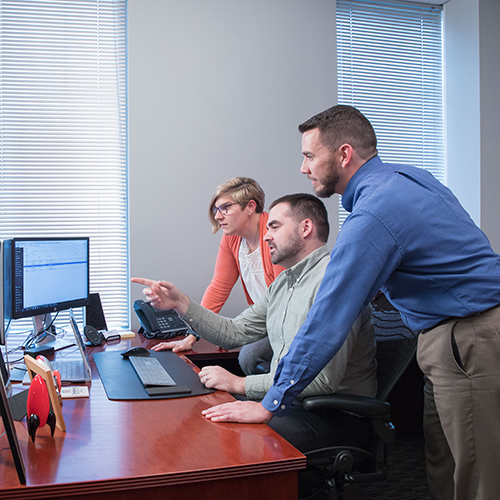 Three Rocket IT team members pointing at and talking about a computer
