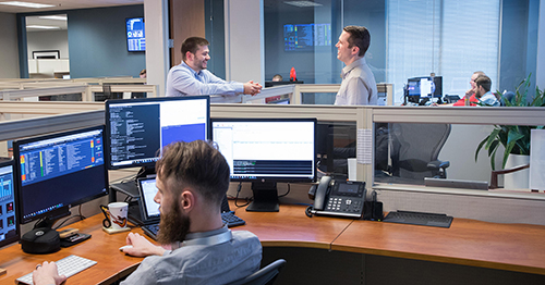 team members collaborating in an office near a desk